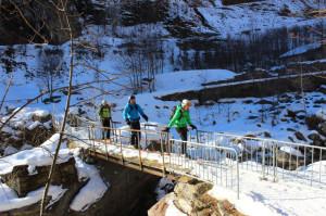 Sciatori su una pista da fondo attraversano un ponticello sulla Sesia.